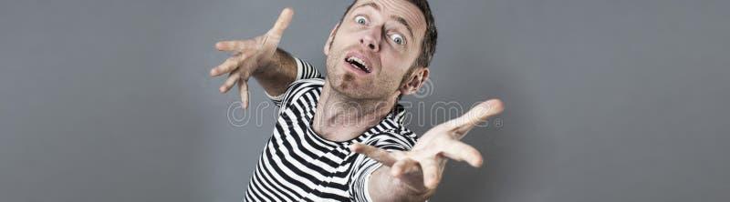 Zdziwiony w średnim wieku mężczyzna celowanie z nadzieją w kierunku niedostępnego celu zdjęcie stock