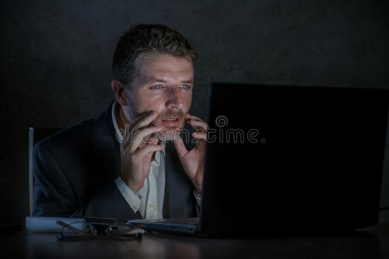 Zdziwiony workaholic przedsiębiorcy mężczyzna pracuje nocnego używa laptop w szoku i niespodzianka z niewiarą stawiamy czoło zdjęcia stock