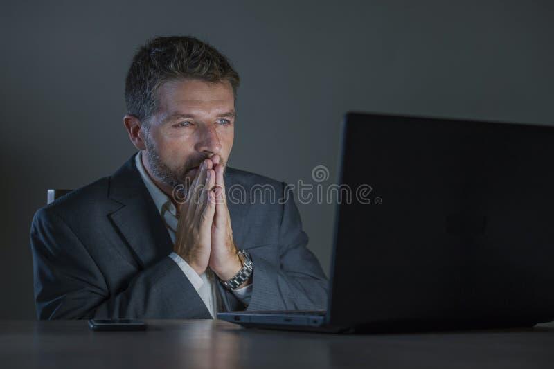 Zdziwiony workaholic przedsiębiorcy mężczyzna pracuje nocnego używa laptop w szoku i niespodzianka z niewiarą stawiamy czoło zdjęcie royalty free
