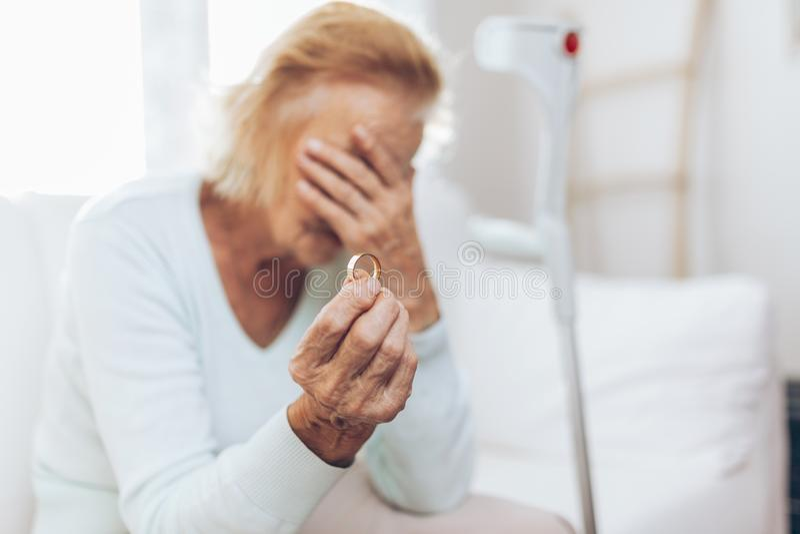 Ze złamanym sercem starsza kobieta trzyma obrączkę ślubną zdjęcia stock