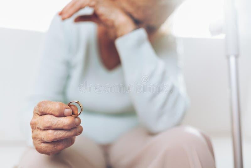 Ze złamanym sercem starsza kobieta trzyma obrączkę ślubną zdjęcie stock