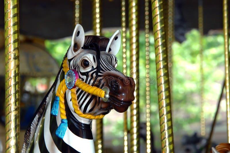 A zebra do carrossel em alegre vai círculo fotografia de stock royalty free