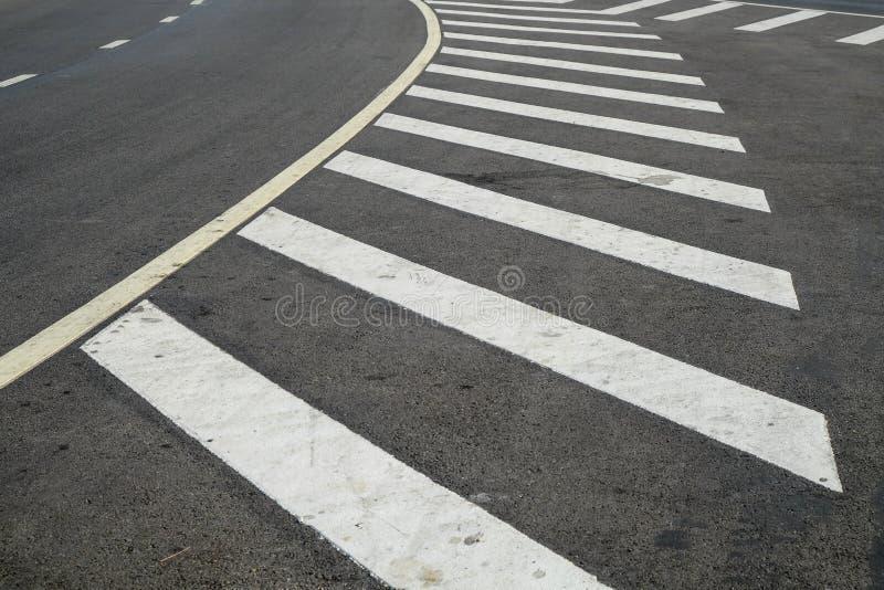 Zebrapad op de weg voor veiligheid wanneer mensen die kruis lopen de straat, voetgangersoversteekplaats op een herstelde asfaltwe stock afbeeldingen