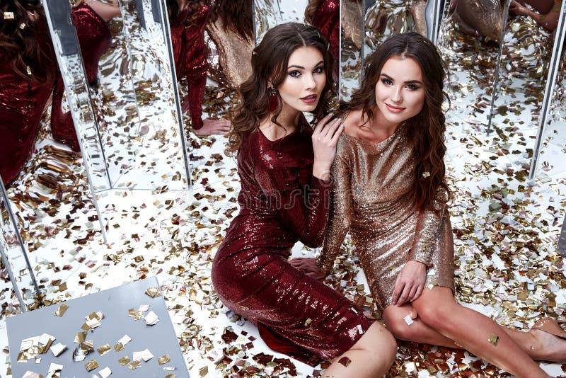 Zecchino brillante del bello di donna due di usura vestito rosso scarno sexy dall'oro fotografia stock