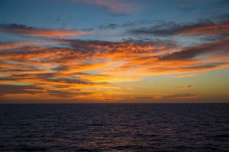 Zeegezicht bij zonsondergang met kleurrijke cloudscape stock foto's