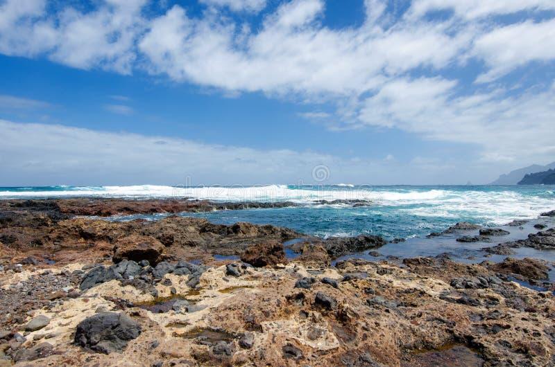 Zeegezicht met mening over de Atlantische Oceaan, de blauwe hemel met witte wolken en steen het wilde strand dichtbij het Landeli stock fotografie