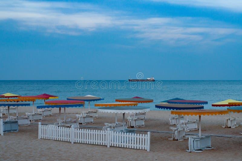 Zeegezicht met niemand en witte ligstoelen gestapeld onder kleurrijke strandparaplu's royalty-vrije stock fotografie