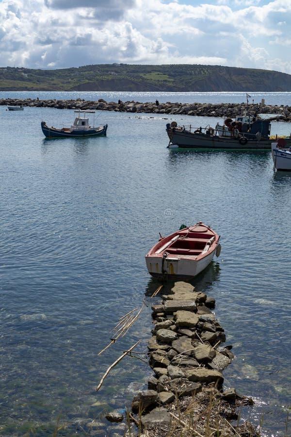 Zeegezicht met pijler, stille overzeese haven met duidelijk transparant water en traditionele Griekse vissersboten stock fotografie