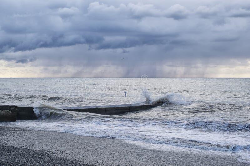 Zeegezicht met pijler tijdens een onweer in de regen met zeemeeuwen royalty-vrije stock fotografie
