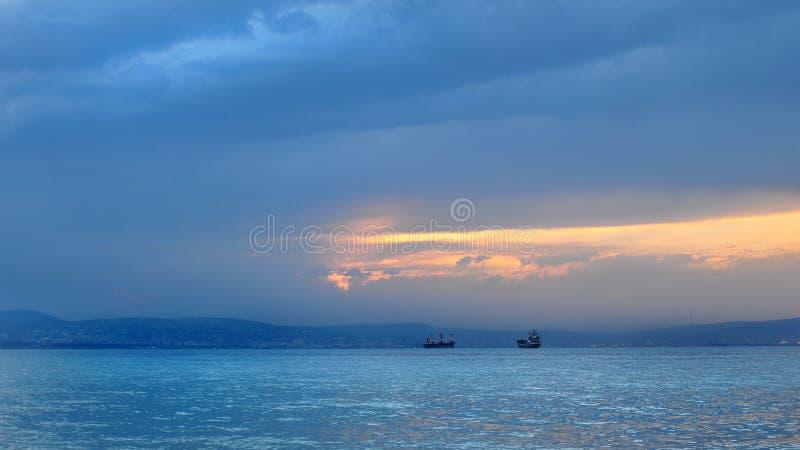 Zeegezicht met prachtige meningen van schepen, bergen, overzees en de het plaatsen zon stock foto's