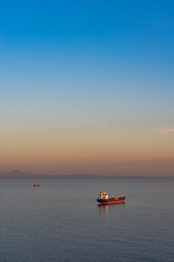 Zeegezicht met tanker en schepen op de achtergrond van het overzees en de kustlijn stock foto