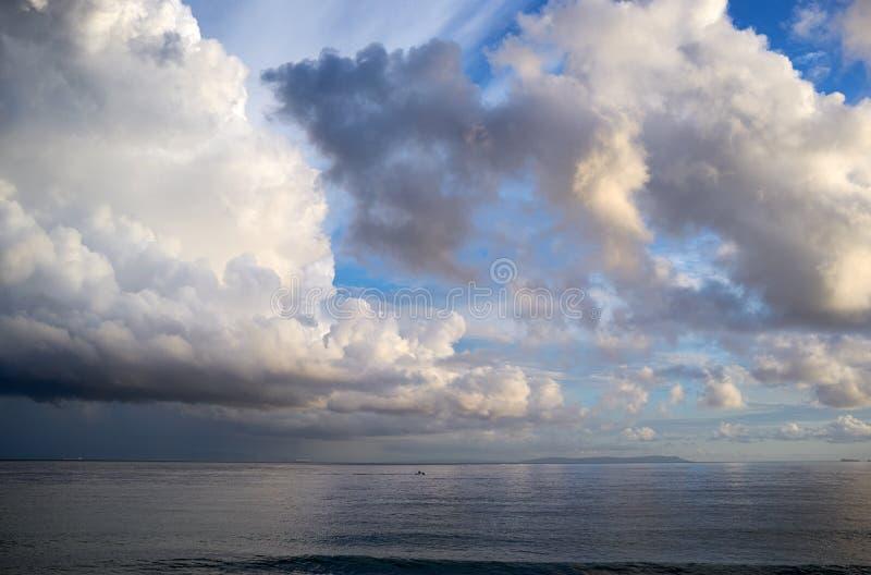 Zeegezicht met torenhoge cumulonimbus wolken stock afbeelding