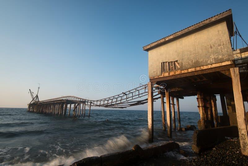 Zeegezicht met verlaten pier tijdens zonsondergang stock foto