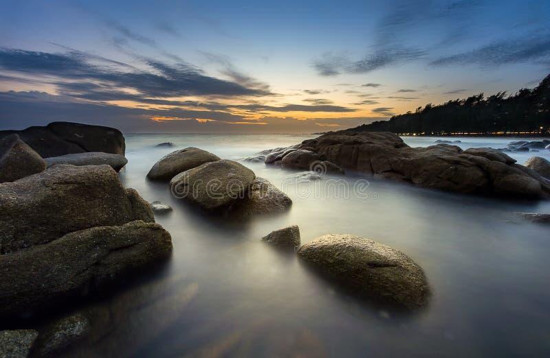Zeegezicht met vlotte golf, rots en zonsondergang stock fotografie