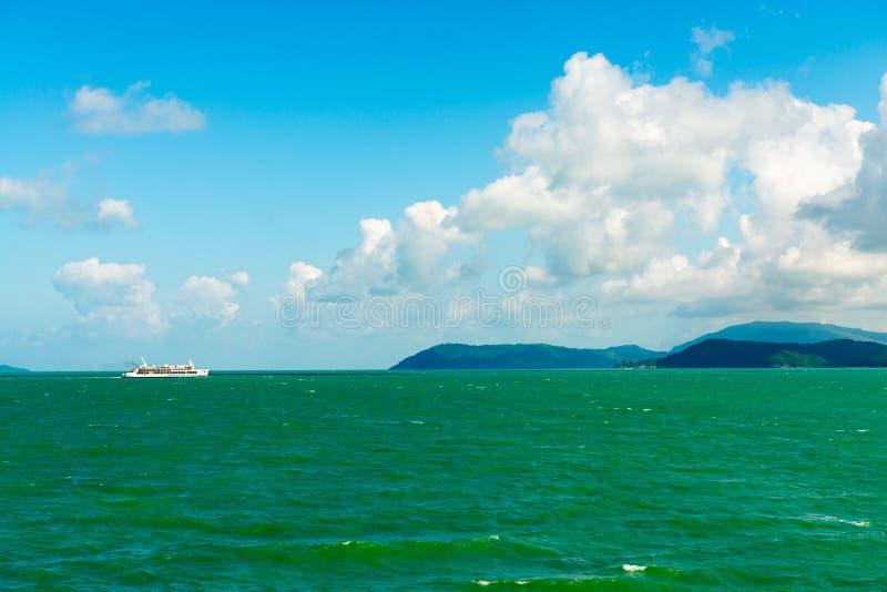 Zeegezicht met witte overzeese veerboot en groene eilanden op horizon stock foto