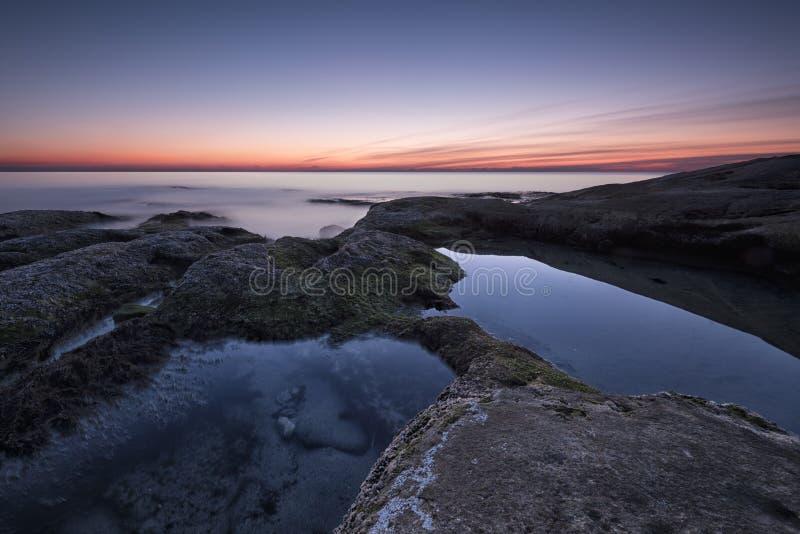 Zeegezicht tijdens Zonsopgang Mooi natuurlijk zeegezicht, blauw uur Rotsachtige zonsopgang Overzeese zonsopgang bij de kust van d stock afbeeldingen