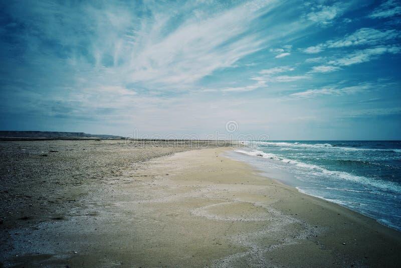 zeegezicht van de verlaten kust aan het Kaspische overzees met blauwe hemel en gebrulgolven royalty-vrije stock foto's