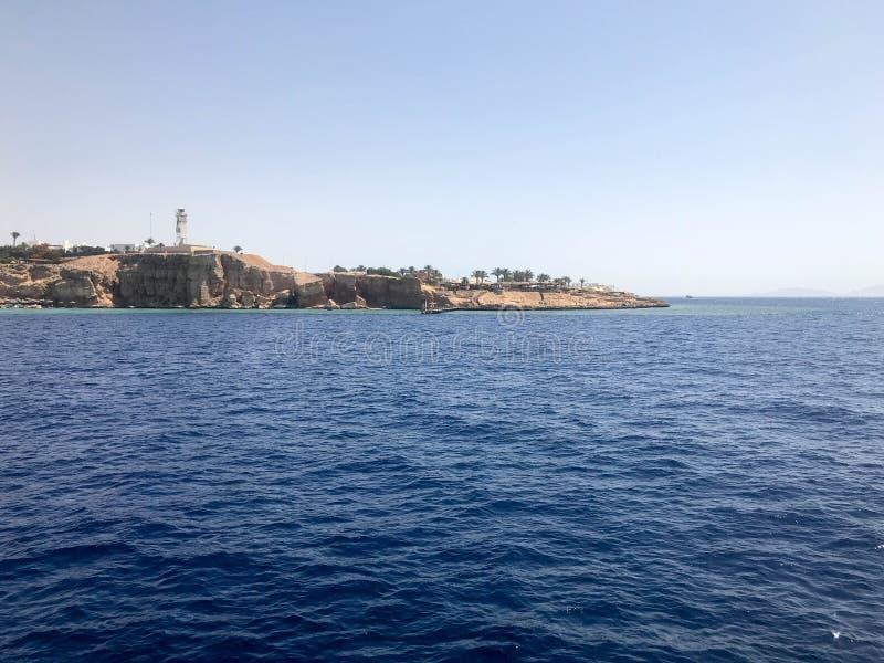 Zeegezicht van de verre mooie tropische bruine steenbergen en de diverse gebouwen op de kust en het blauwe zoute azuurblauwe over royalty-vrije stock foto's