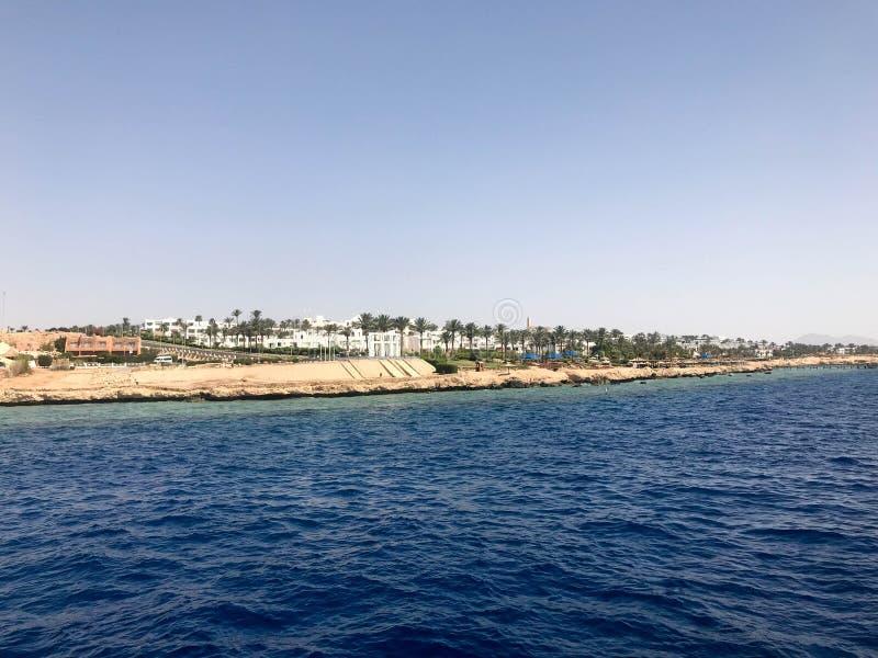 Zeegezicht van de verre mooie tropische bruine steenbergen en de diverse gebouwen op de kust en het blauwe zoute azuurblauwe over royalty-vrije stock afbeeldingen