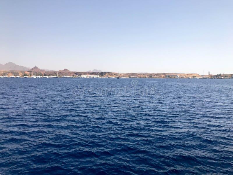 Zeegezicht van de verre mooie tropische bruine steenbergen en de verschillende huizen, de gebouwen op de kust en blauwe zoute azu stock foto