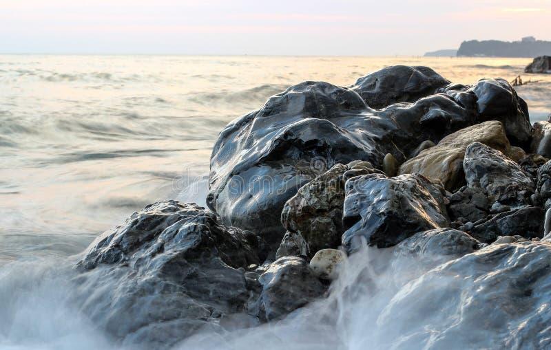 Zeegezicht, zwarte natte stenen, overzeese golf, de stenen op de kust royalty-vrije stock foto's
