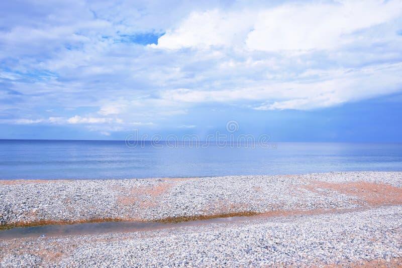 Zeegezichtstrand dat met Foto het Landschaps van de van de Achtergrond zeeschelpenkust de Toneelbehangvoorraad wordt behandeld stock foto