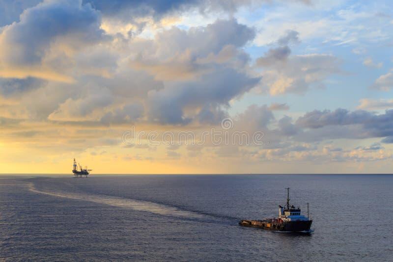 Zeehefboom op boringsinstallatie en leveringsboot royalty-vrije stock afbeeldingen