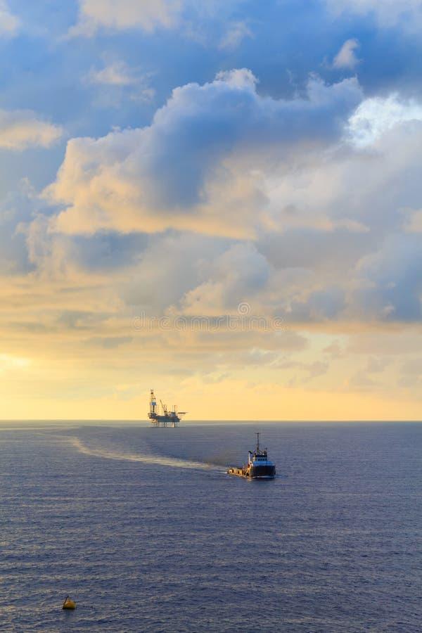 Zeehefboom op boringsinstallatie en leveringsboot stock fotografie