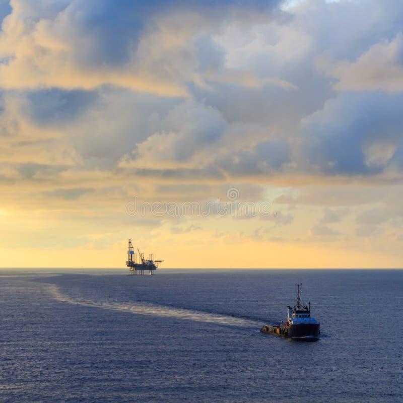 Zeehefboom op boringsinstallatie en leveringsboot royalty-vrije stock fotografie