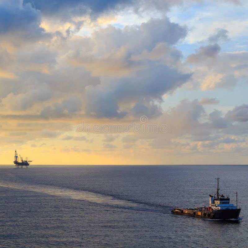 Zeehefboom op boringsinstallatie en leveringsboot royalty-vrije stock afbeelding