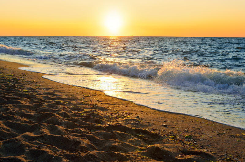 Zeekust op een achtergrond van de het toenemen zon stock afbeeldingen