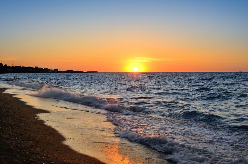 Zeekust op een achtergrond van de het toenemen zon stock foto