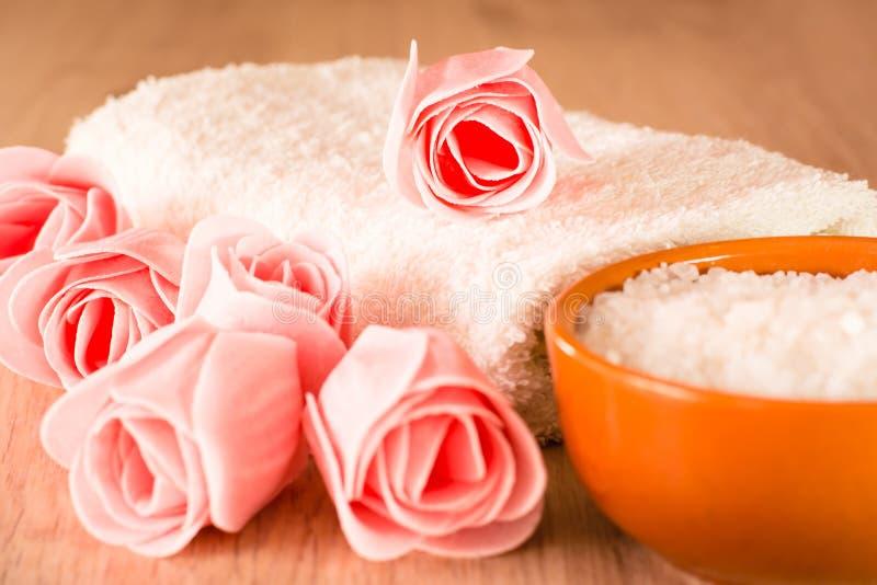 Zeep in de vorm van bloemen, overzees zout in de kom en handdoek stock afbeelding