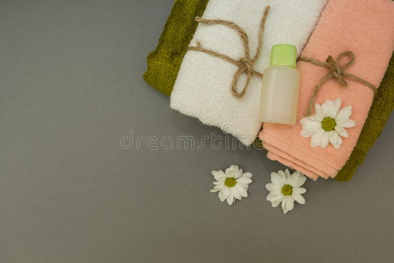 Zeep, handdoek en bloemensneeuwklokjes Bloembloemblaadjes op grijze achtergrond royalty-vrije stock foto