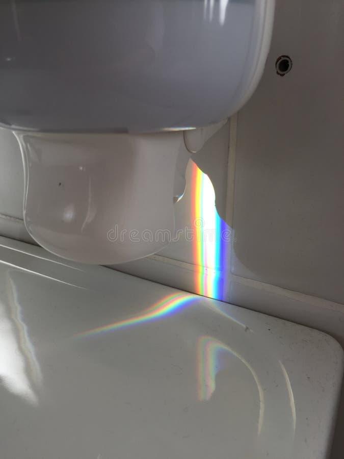 Zeepautomaat boven wasbassin met vuil en mooi regenbooglicht stock afbeelding