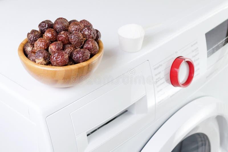Zeepnoten in een kom op de wasmachine en detergent poeder, selectieve nadruk stock afbeeldingen