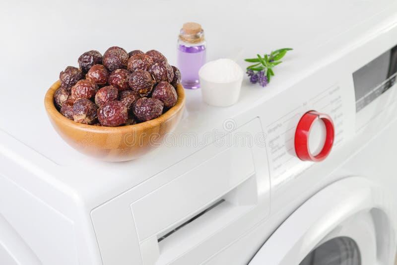 Zeepnoten in een kom op de wasmachine en lavendelolie, detergent poeder, selectieve nadruk royalty-vrije stock foto's