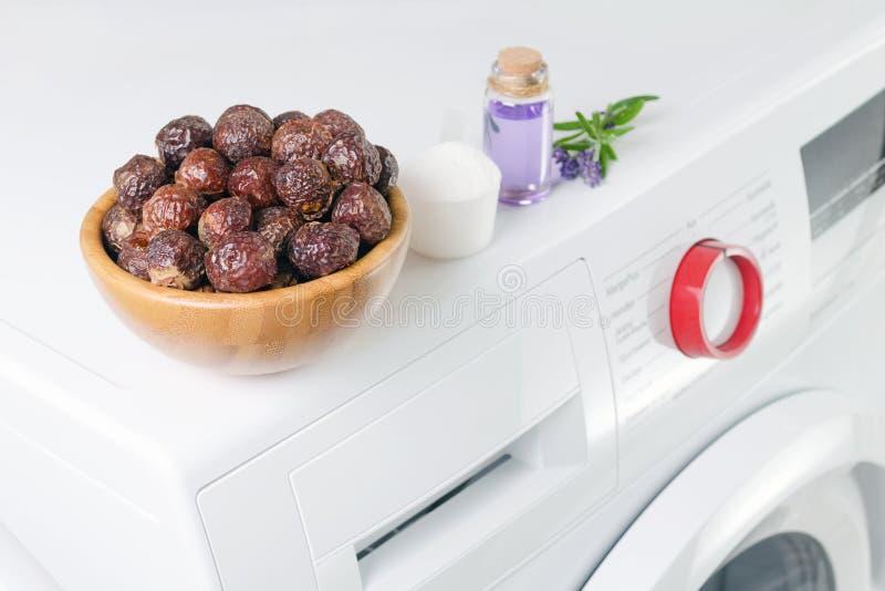 Zeepnoten in een kom op de wasmachine en lavendelolie, detergent poeder, selectieve nadruk stock afbeelding