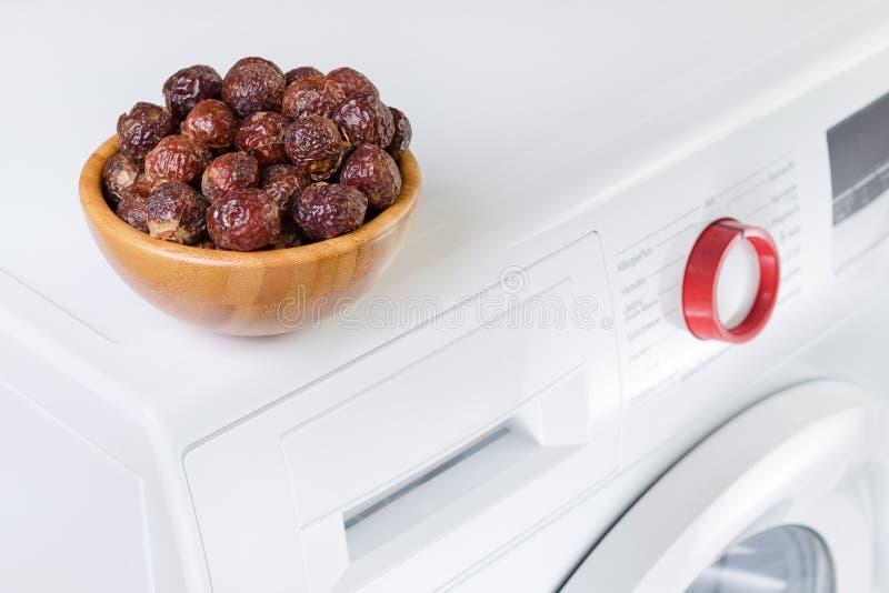 Zeepnoten in een kom op de wasmachine, organische detergent, selectieve nadruk stock afbeeldingen