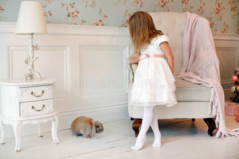 Zeer aardig charmant meisjeblonde in een witte kleding status royalty-vrije stock foto's