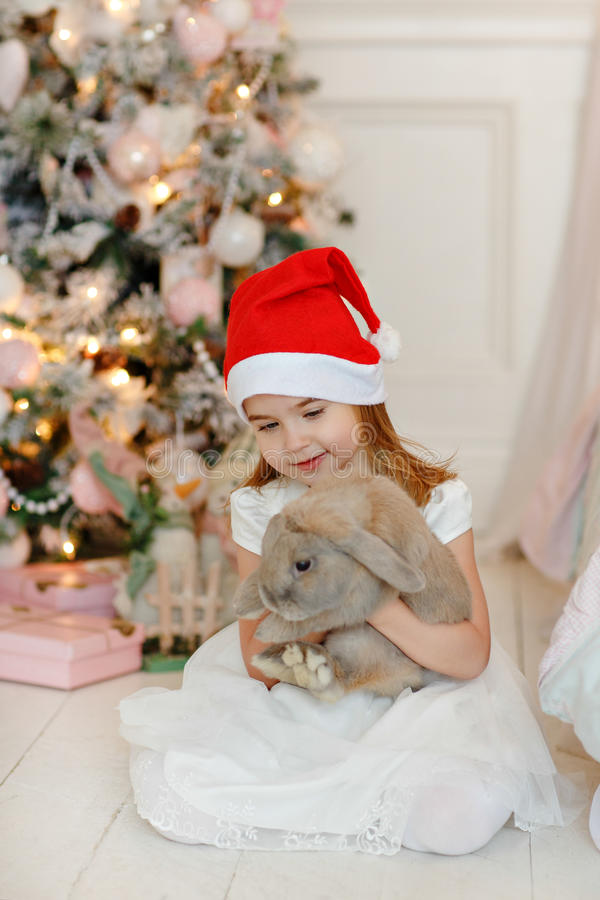 Zeer aardig charmant meisjeblonde in witte kleding en Kerstman h royalty-vrije stock foto's