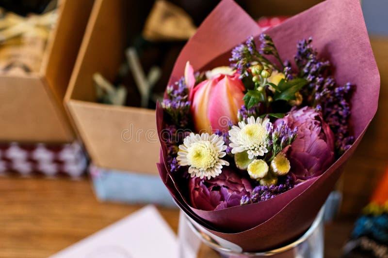 Zeer aardige bloemistvrouw die een mooi kleurrijk tot bloei komend bloemboeket van pioen, anjers, rozen, eustoma houden royalty-vrije stock afbeeldingen