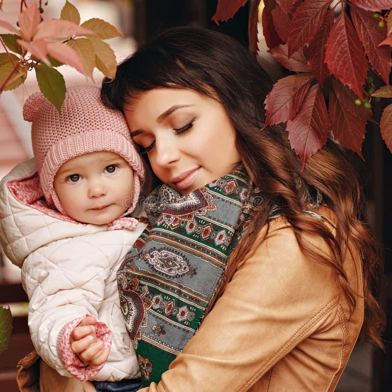 Zeer charmante mooie donkerbruine moeder met het gesloten ogen houden royalty-vrije stock fotografie