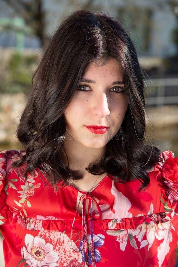 Zeer close-upportret van het gezicht van een meisje met lang zwart haar, groene ogen, rode lippen stock afbeelding