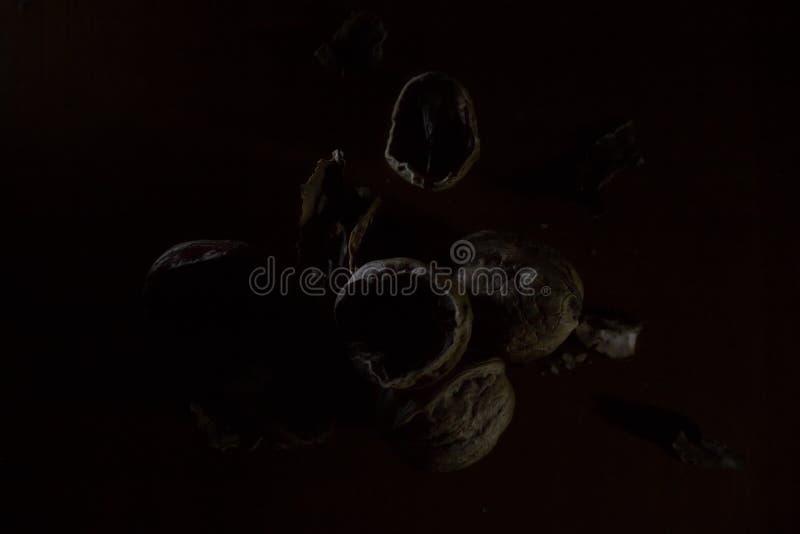 Zeer donker boven geschoten van gebarsten okkernootshells op de lijst royalty-vrije stock afbeelding