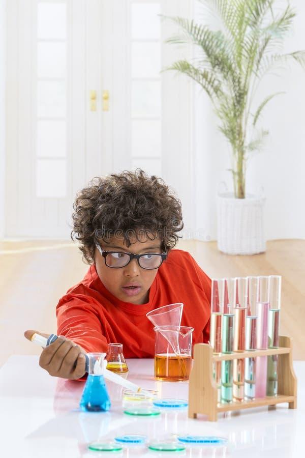 Zeer ernstig leuk jong geitje met ogenglazen die chemieexperimenten doen de fles van de jongensholding en reageerbuis in handen stock fotografie
