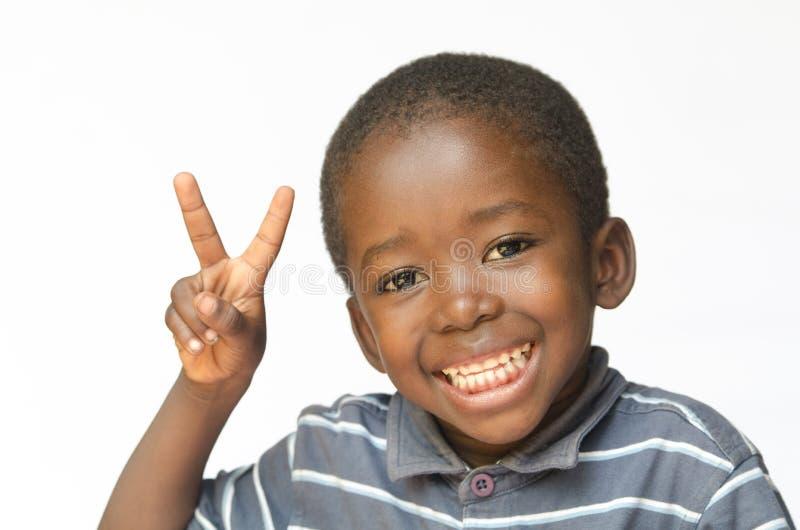 Zeer gelukkige Afrikaanse zwarte jongen die vredesteken voor vrede van de het behoren tot een bepaald ras reusachtige glimlach va royalty-vrije stock afbeeldingen
