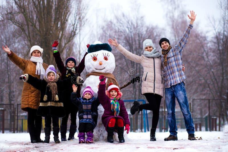 Zeer grote familie van drie generaties: de grootmoeder, de vader, de moeder en de dochters beeldhouwen grote echte sneeuwman Gelu stock fotografie