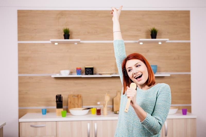 Zeer het gelukkige roodharigevrouw zingen in de keuken stock foto