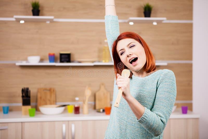 Zeer het gelukkige roodharigevrouw zingen in de keuken royalty-vrije stock foto's